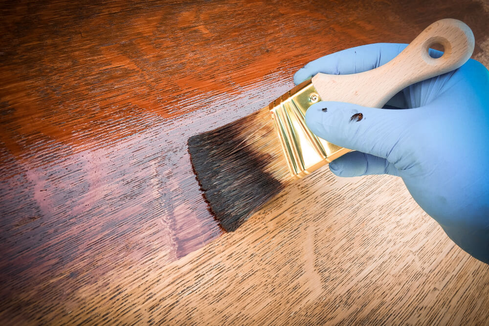 applying finish to wooden board