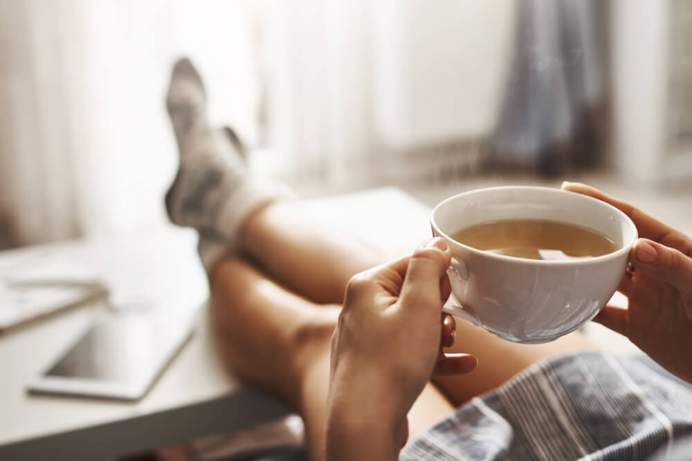 woman indoors with warm cup of tea