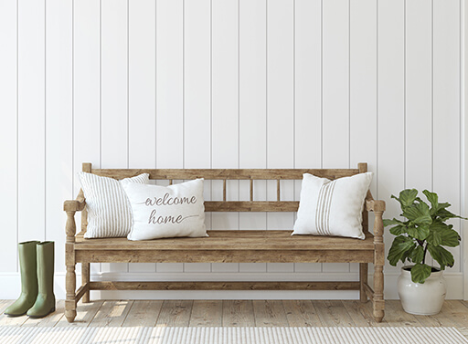 Image of a bench with a welcome home pillow against white vertical paneling.
