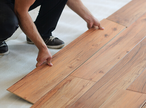 Laying down slats of laminate flooring on an angle to fit into the tongue grooves